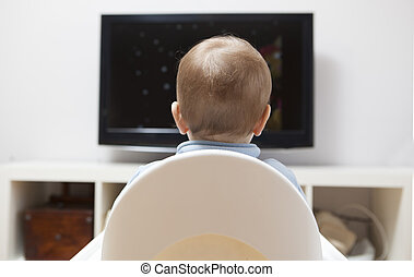 Baby boy watching cartoons on TV. He is sitting on his...