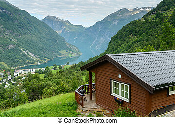 Beautiful view at fiord with wooden cabin at foreground -...