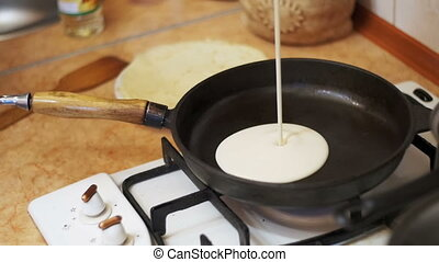 The Dough Falls on the Hot Skillet. Cooking Pancakes in a...