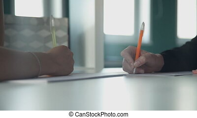 Two people at the table to quickly write pen on paper in the...