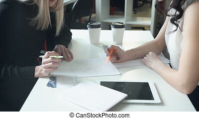 Two women at a table on a paper written jointly handle the...