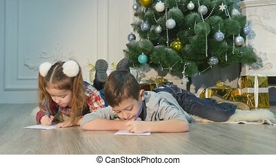 Children write letters to Santa Claus. To children it is cheerful. Little boy and girl lie on a floor near Christmas tree. House is festively decorated.