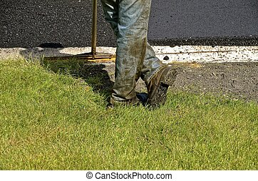 Asphalt worker leans on a shovel - An asphalt construction...