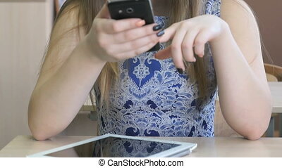 Schoolgirl writes message using mobile phone - Schoolgirl...