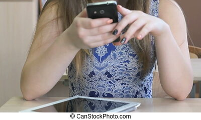 Schoolgirl holding mobile phone. Close-up - Schoolgirl aged...