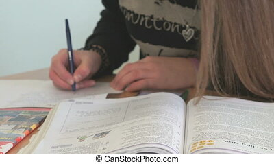 Girl writes the text on a white sheet of paper - The girl...