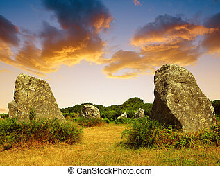 Megalithic monuments menhirs in Carnac at sunset - Brittany,...