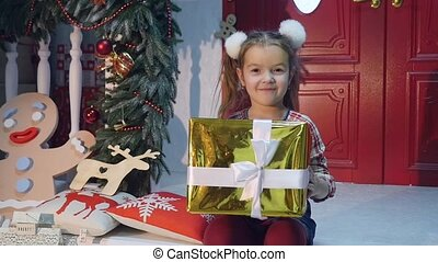 young girl giving a present to camera