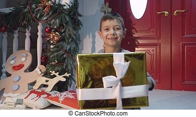 young boy giving a present to camera.