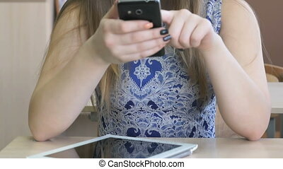 Schoolgirl writes message using smart phone - Schoolgirl...