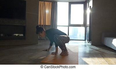 Girl practicing yoga in the living room Attractive woman do...