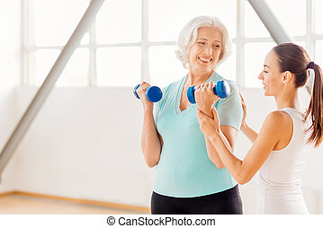 Delighted aged woman holding dumbbells