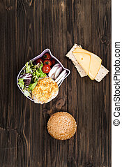 Vertical photo of sandwich and salad standing on the desk