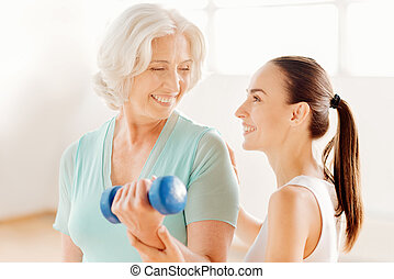 Nice fitness coach helping the elderly woman