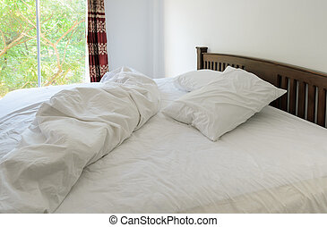Morning view of an unmade bed in white bedroom with open...