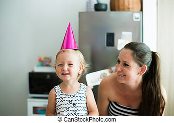 Beautiful mother with her cute daughter wearing party hat -...