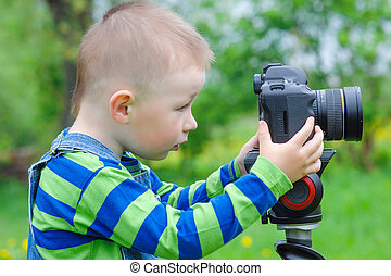 little boy takes off on a photo camera.