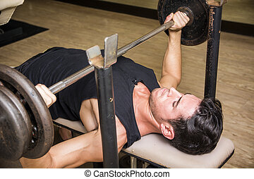 Handsome young man using barbell in gym