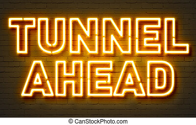 Tunnel ahead neon sign on brick wall background.