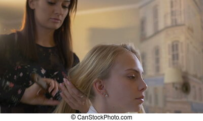 Hair stylist makes hairstyle to girl