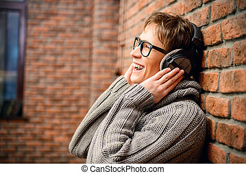 happy music - Happy young man listens to music in headphones...