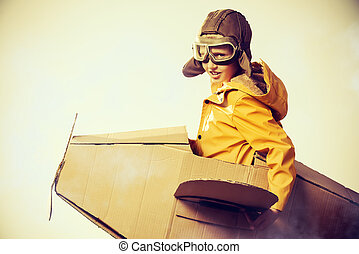 game with airplane - Eight-year boy playing with a cardboard...