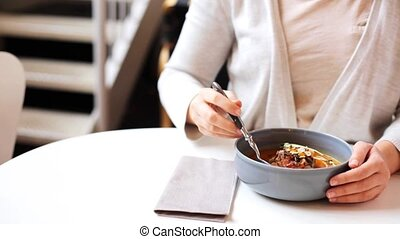woman eating pumpkin cream soup at restaurant - food, new...