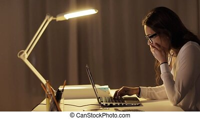 tired woman in glasses with laptop at night office -...