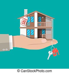 Hand with small house, keys and price tag. Buying or selling...