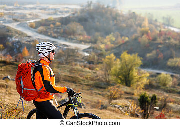 Young bicyclist standing near and looking to mountains