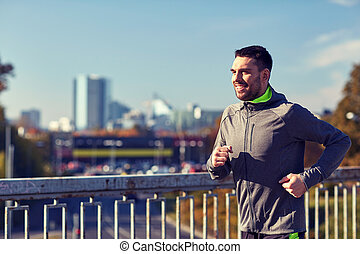 happy young man running over city bridge - fitness, sport,...