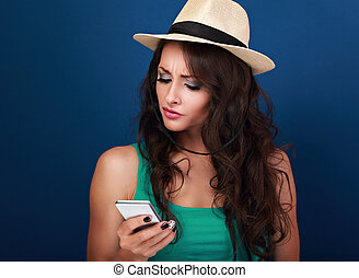 Unhappy angry woman in hat looking on mobile phone in stress...