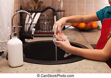 Washing the dishes - child hands cleaning a glass with...
