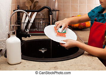 Child washing a plate with sponge at the kitchen sink,...