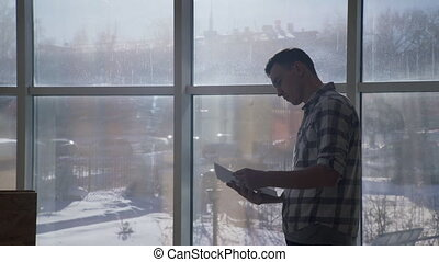 Man at the window looking documents that iterates over in his hands.