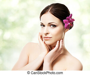 Close-up portrait of beautiful, fresh, healthy and sensual girl with an orchid flower in her hair. Health, treatment, spa concept.