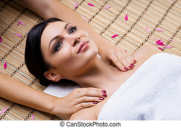 Beautiful, young and healthy woman on bamboo mat in spa salon having shoulders massage. Spa, health and healing concept.