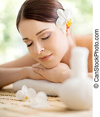 Young and beautiful girl relaxing in spa salon. Massage...