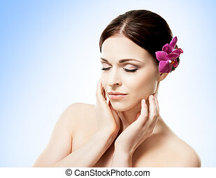 Close-up portrait of a beautiful girl with an orchid flower in her hair. Health, treatment, spa concept.
