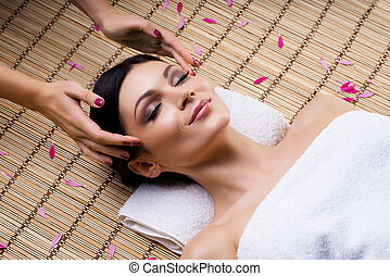 Beautiful, young and healthy woman on bamboo mat in spa salon having temple massage. Spa, health and healing concept.