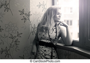 Attractive girl looks out the window
