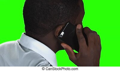 Phone talk on green background. Black man with smartphone.