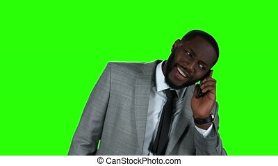 Smiling black businessman with phone.