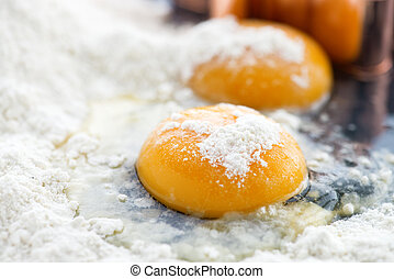 close up of two egg yolks in flour ,focus on the foreground...
