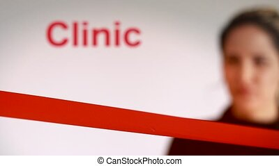 Woman cutting red ribbon at a clinic