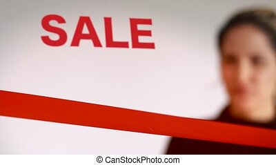 Woman cutting red ribbon with sale sign