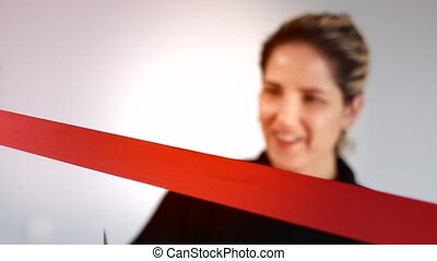 Amiling woman cutting red ribbon