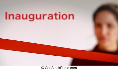 Woman cutting red ribbon at an inaguration event - Woman...