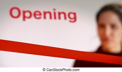 Woman cutting red ribbon at an opening event - Woman cutting...