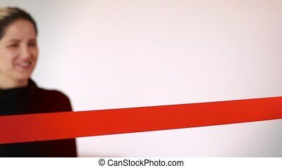 Woman cutting red ribbon with abstract white background